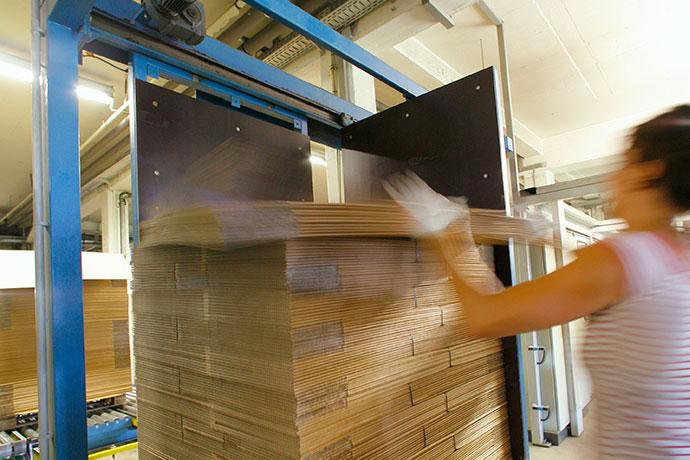 Frau stapelt gefaltete Kartons